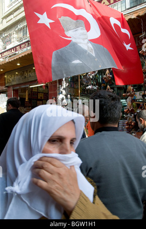 Veiled woman and  the image of Kemal Ataturk in a flag  near the the Misir Carsisi (Egyptian bazaar). Istanbul. - Stock Photo