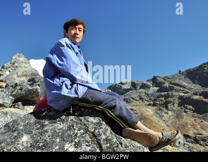 Handsome young Nepalese man sitting on a rock staring into the distance - Stock Photo