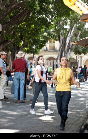 attractive Mexican woman & her pretty tween daughter chasing after a long tubular balloon in Oaxaca City Zocalo - Stock Photo