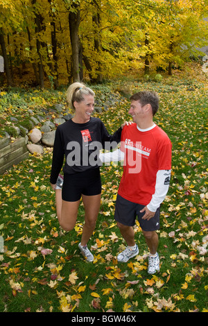 Young, smiling couple stretches before jogging - Stock Photo