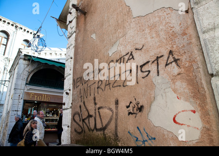 Tourists looking at graffiti on the wall in Venice, Italy - Stock Photo