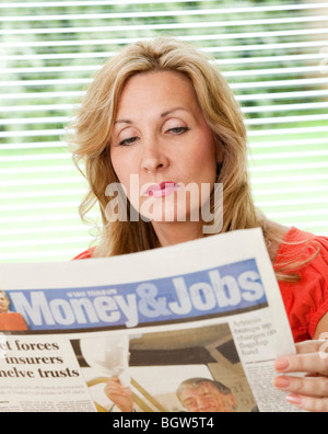 young woman reading a newspaper looking for a new job - Stock Photo