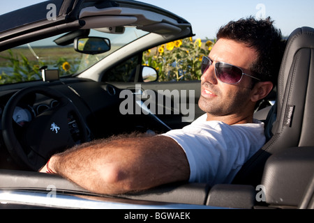 Charmant ... A Cool Man On A Convertible Car Driving Near A Sunflower Field   Stock  Photo