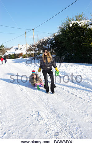 Children with sledges in the Snow in Stonesfield,a village in Oxfordshire being pulled by their mother - Stock Photo