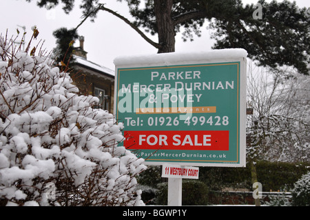 House sale sign in snowy weather, UK - Stock Photo