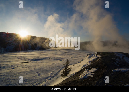 Steam rises from thermal springs on the Main Terrace providing a dramatic winter sunrise over Mt. Everts -Mammoth - Stock Photo