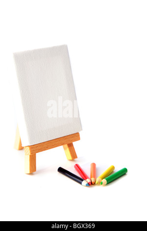 Several colorful pencils lying next to a scaffold. All on white background. - Stock Photo