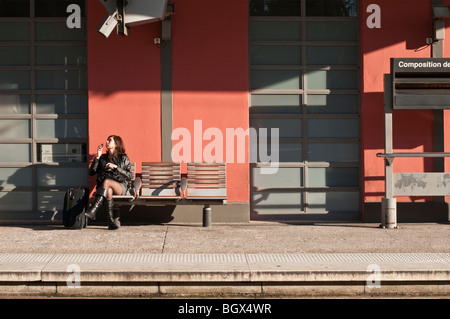 Young woman awaiting a train at a railway station in southern France - Stock Photo