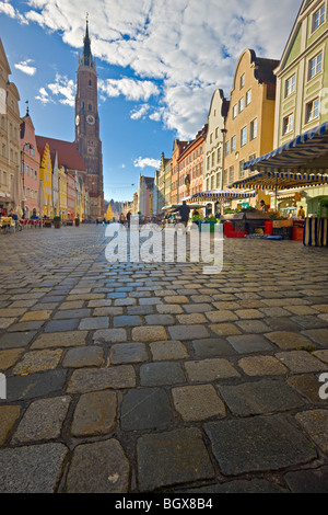 Bell tower of Martinskirche (St Martin's Church) and the colorful facades of buildings along a cobbled street in - Stock Photo