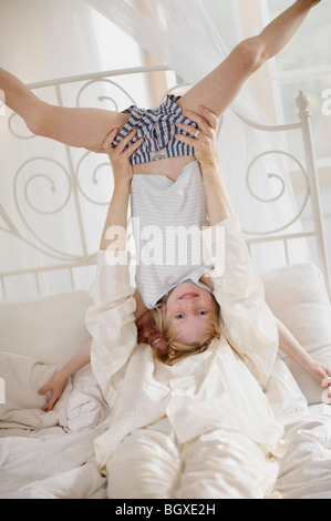 Father holding son upside down in bed - Stock Photo