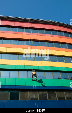 One office Window cleaner suspended high up in a seat harness on an Abseiling Rope washing windows, Warsaw, Poland, - Stock Photo