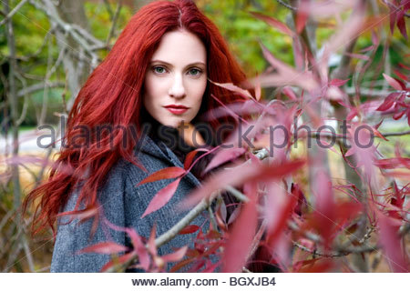 A young woman standing behind a tree in autumn time - Stock Photo