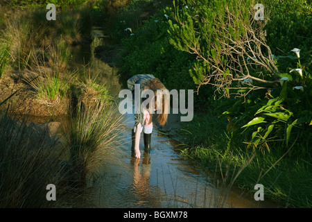Girl bending down in stream - Stock Photo