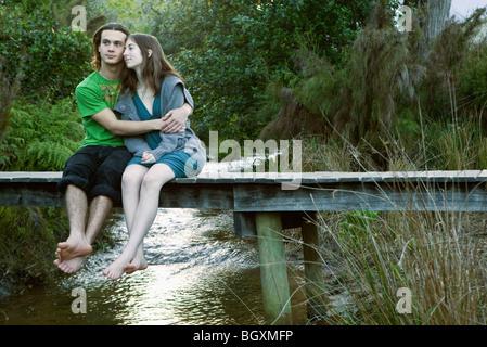 Young couple sitting on bridge - Stock Photo
