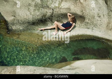 Girl lying on rock next to stream - Stock Photo