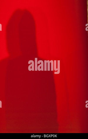 Shadow of figure human, speaker, against a red backdrop, at a conference. - Stock Photo