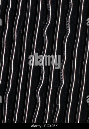 The grooves on a 45RPM stereo single vinyl record photographed at 25x resolution - Stock Photo