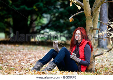 A young woman sitting beneath a tree in autumn time - Stock Photo