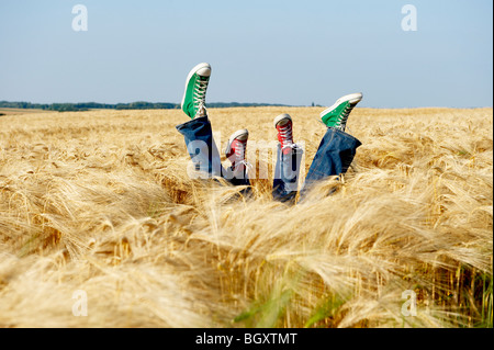 Feet sticking out from a wheat field - Stock Photo