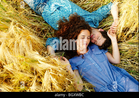 Couple laying down in a wheat field - Stock Photo