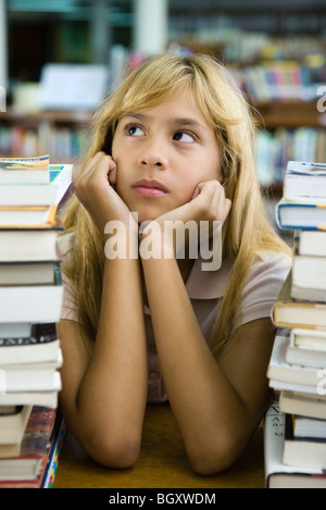 Preteen girl sitting with two large stacks of books, chin in hands, looking away