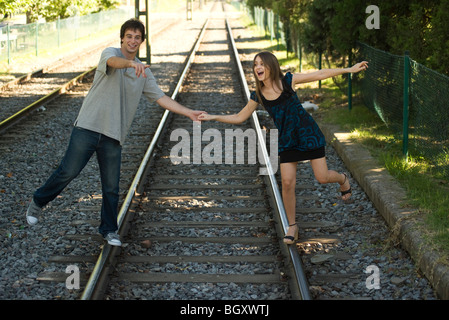Young couple walking on rail track, holding hands - Stock Photo
