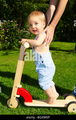 Baby boy on scooter in the garden - Stock Photo