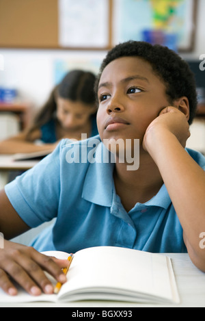 African-American male student sits alone at table during ...
