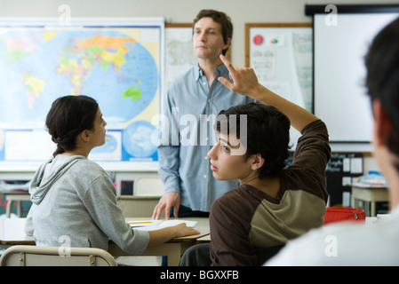 High school student raising hand in class, looking over shoulder - Stock Photo