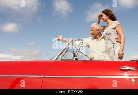 Senior couple in sports car, pointing - Stock Photo