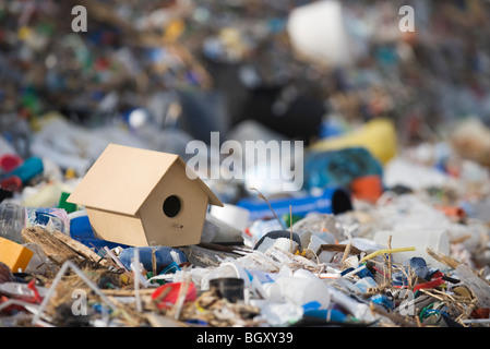 Birdhouse on ground surrounded by landfill trash - Stock Photo