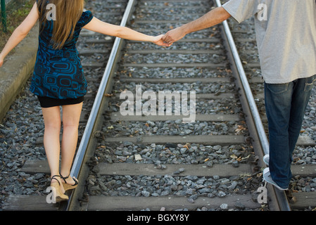 Young couple holding hands walking on rail track, rear view - Stock Photo