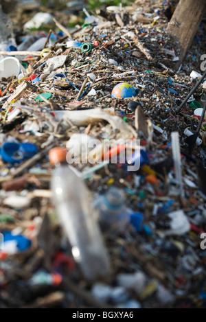 Globe in midst of landfill trash - Stock Photo