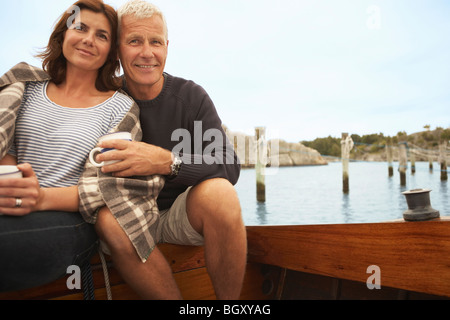 Middle aged couple cuddling on old boat - Stock Photo