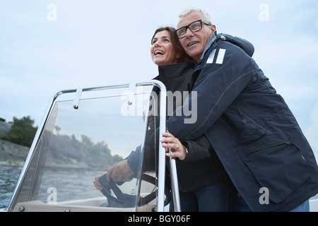 Middle aged couple on motor boat - Stock Photo