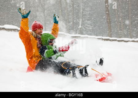Mother and son sledding in a fresh snowfall. - Stock Photo