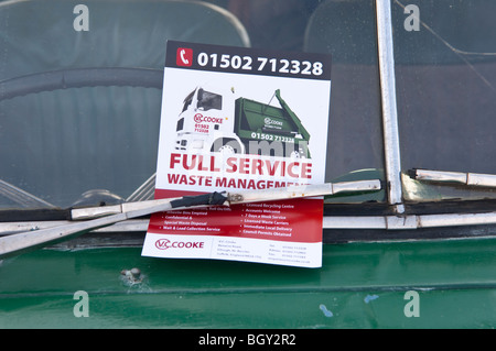 A flyer advertising full service waste management on a car windscreen in Suffolk , England , Britain , Uk - Stock Photo