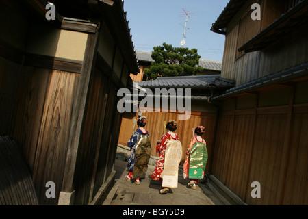 Three girls dressed as 'maiko/geisha' girls walk down Ishibe-Koji Street, in the Gion district of the city famous - Stock Photo