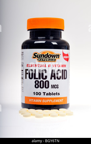 A closed unopened bottle of Sundown Naturals Folic Acid vitamins with some pills spilled on white background.