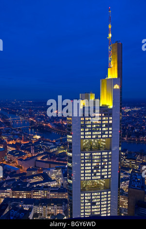 Commerzbank Tower illuminated with yellow lights at dusk as seen from the Main Tower in the City of Frankfurt am - Stock Photo