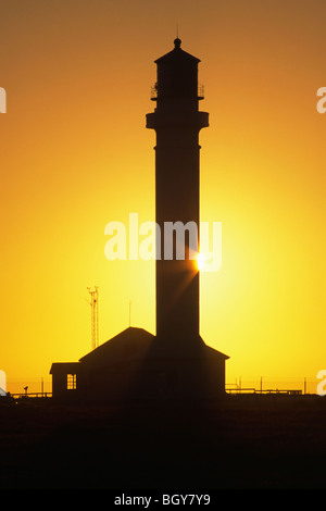 The sun sets behind the silhouette of the Point Arena Lighthouse on the Northern California Coast south of Mendocino. - Stock Photo
