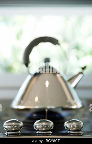 Tea kettle on gas stovetop - Stock Photo