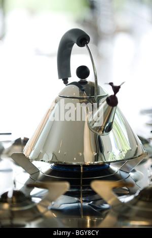 Tea kettle heating on gas stove - Stock Photo