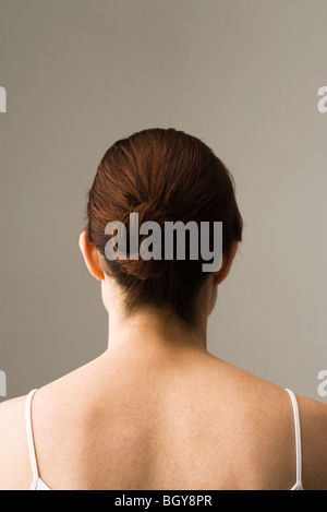 Woman with hair arranged in chignon, rear view - Stock Photo