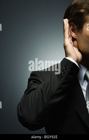 Man with hand cupped around ear listening attentively - Stock Photo
