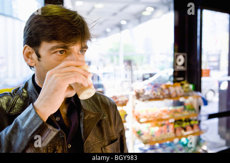 Man drinking coffee in convenience store - Stock Photo