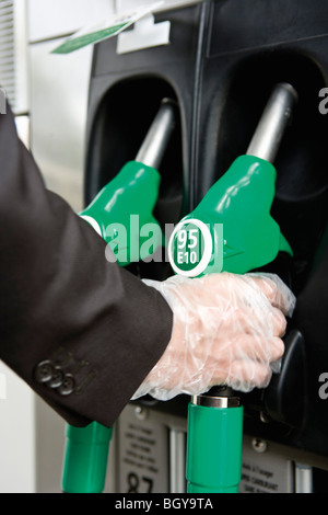At gas pump with gloved hand removing nozzle - Stock Photo