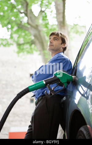 Well-dressed man refueling vehicle at gas station - Stock Photo