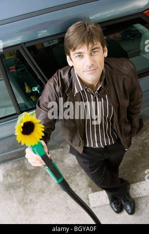 Man at gas station holding gas nozzle with sunflower emerging from end - Stock Photo