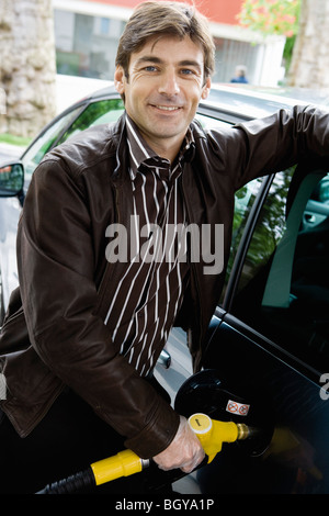 Man refueling vehicle at gas station - Stock Photo